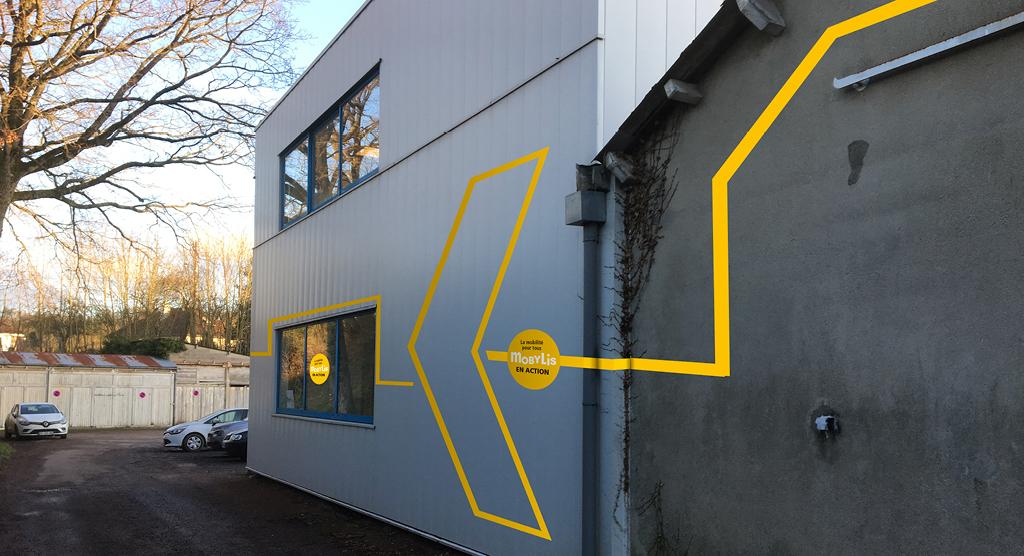 Exemple de la signalétique modulaire imaginée pour Mobylis installée sur la façade extérieure d'un batiment. Bandes adhésives jaunes et cercles adhésifs avec inscription «la Mobilité pour tous, Mobylis en action». La disposition des élements dessine une très grande flèche et trace un itinéraire jusqu'à l'entrée.