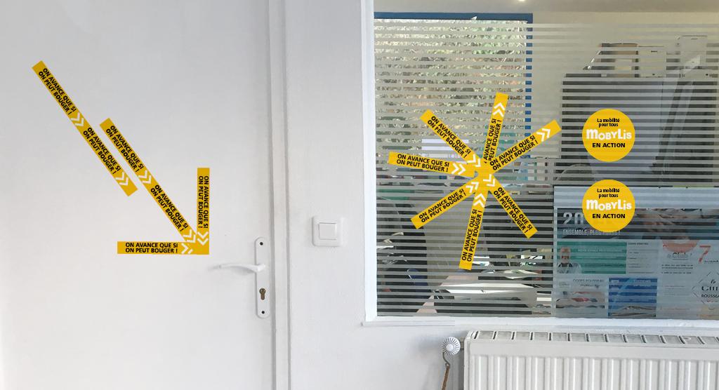 Exemple de la signalétique modulaire imaginée pour Mobylis sur une porte et une vitre. Bandes adhésives avec le slogan «on avance que si on peut bouger» et cercles adhésifs avec inscription «la Mobilité pour tous, Mobylis en action». la disposition des éléments dessine des flèches et un astérisque.